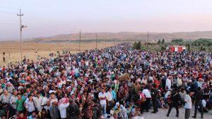 Afbeelding van drommen mensen op een weg, mogelijk vluchtelingen